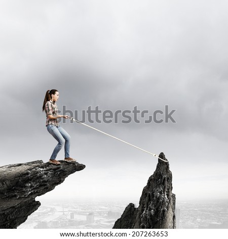 Young woman climbing rock with help of rope