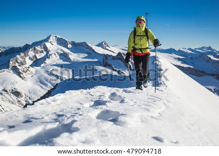 Young woman climbing snow ridge in the Alps