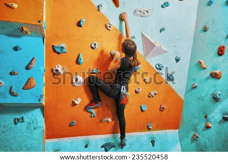 Young woman climbing up on practice wall in gym, rear view - stock photo