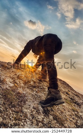 Young woman climbs a rocky hill - stock photo