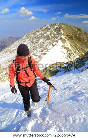Young woman climbs on snowy mountain in fine winter day - stock photo