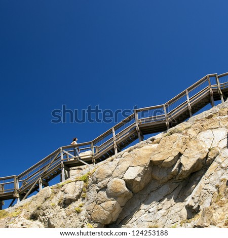 Young woman climbs up steep stairs on a mountain with blue sky behind as copy space