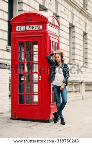 Young woman close to red telephone box in London. Full body portrait. - stock photo