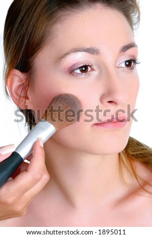 Young woman, close up, applying blusher