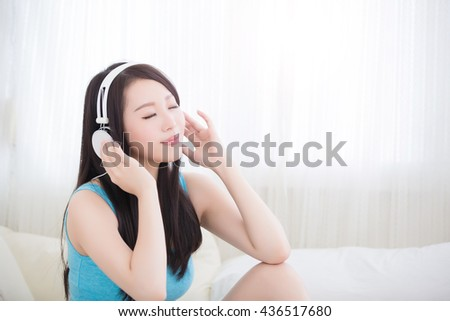 Young woman closed eye and enjoying the music and relax sit at home, asian beauty - stock photo