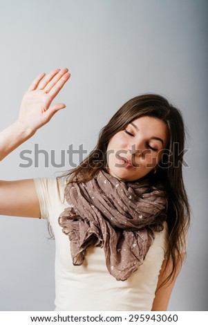 Young woman closed her eyes, shows displeasure leave me alone. On a gray background. - stock photo