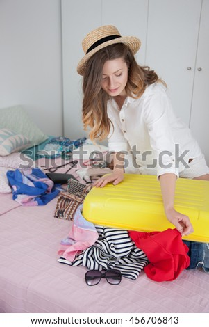 Young woman collects a suitcase at home.The girl in the bedroom, a lot of things, vacation and yellow suitcase