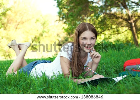 Young woman college student with book and bag studing in a park