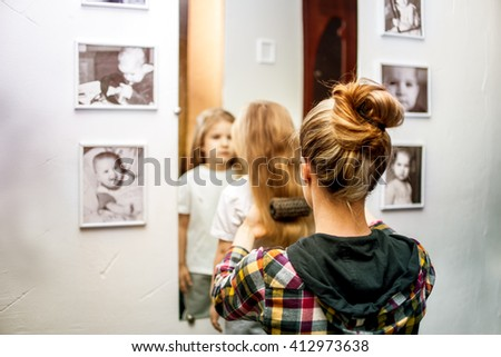 Young woman combing child five years old near the mirror - stock photo