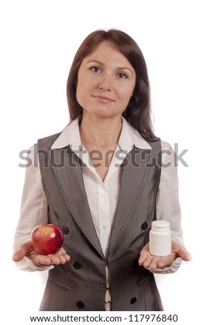 Young woman comparing apple with medicine over white background - stock photo