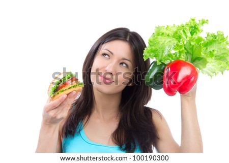 Young woman comparing tasty fast food unhealthy burger or hamburger and healthy fresh peppers and salad isolated on a white background - stock photo