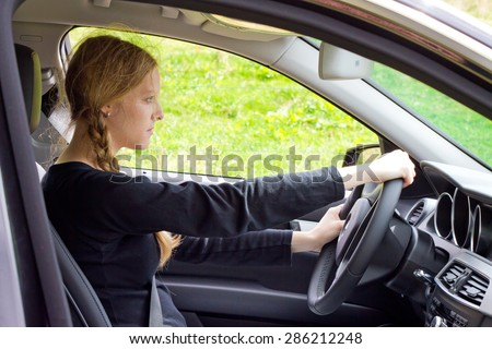 Young woman concentrate in a car - stock photo