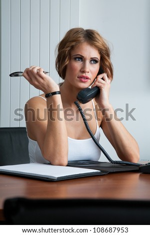 Young woman concentrating using phone in office