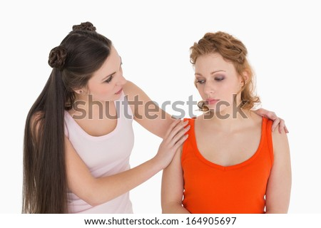 Young woman consoling female friend over white background