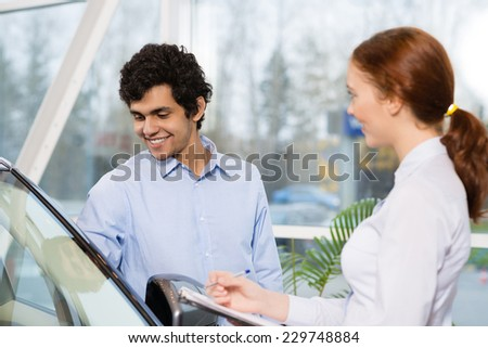 Young woman consultant in show room talking with client