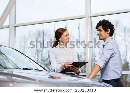 Young woman consultant in show room talking with client - stock photo