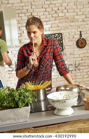 Young woman cooking at home, thinking. - stock photo