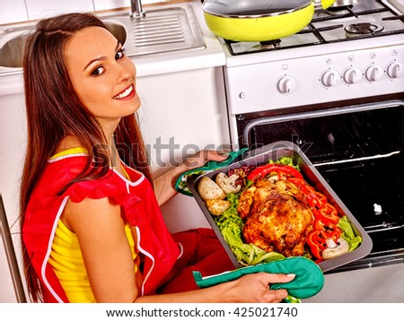 Young woman cooking chicken at kitchen. Woman going to cook chicken in oven.