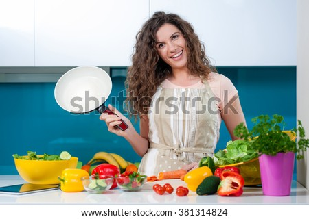Young woman cooking healthy food holding a pan. Healthy lifestyle, cooking at home concept. - stock photo