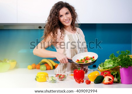 Young woman cooking healthy food holding a pan with vegetables is it. Healthy lifestyle, cooking at home concept. - stock photo