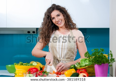 Young woman cooking in the kitchen healthy food, vegetable Salad. Holding a knife and cutting vegetables on a cutting board. Healthy lifestyle cooking at home. - stock photo