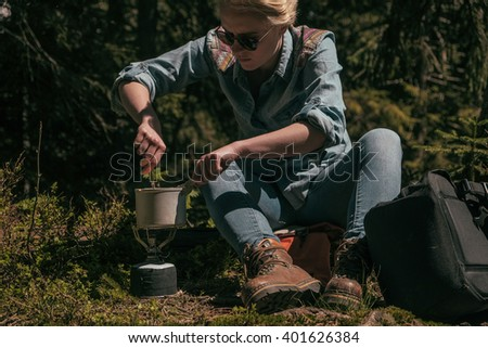 young woman cooking on outdoor gas cooker