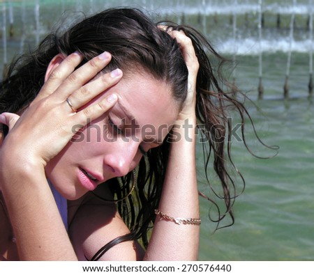 young woman cooling near the fountain in hot day           - stock photo