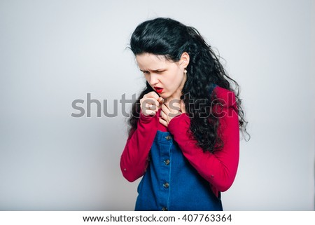 young woman coughs, dressed in a overalls, close-up isolated on a gray background - stock photo