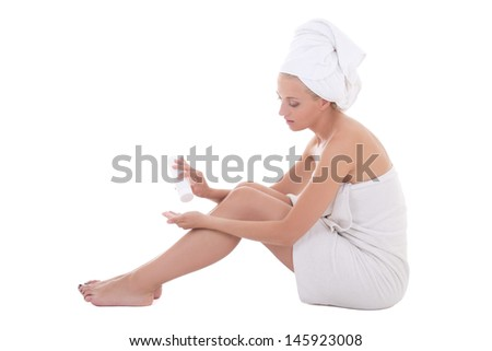young woman covered in towel with body lotion isolated over white background - stock photo