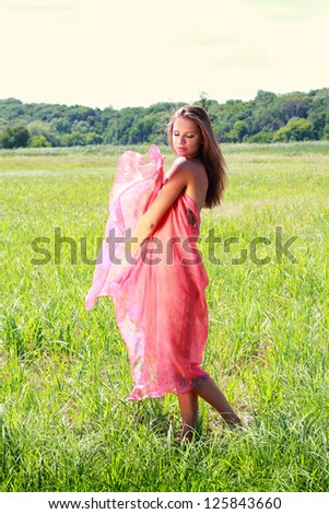 Young woman covered with red fabric walking on green valley - stock photo