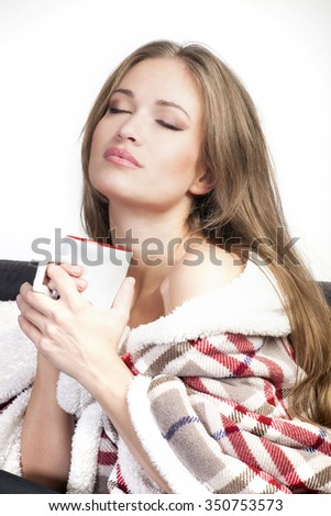 young woman covered with warm blanket enjoy in cup of tea or coffee
