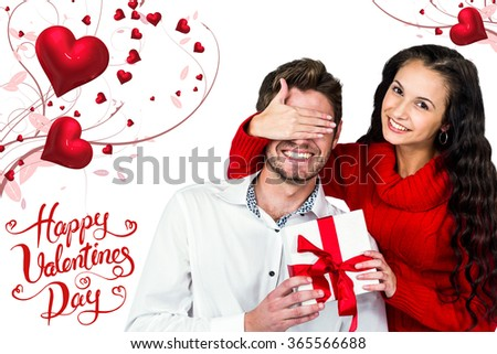 Young woman covering eyes of partner holding gift against happy valentines day - stock photo