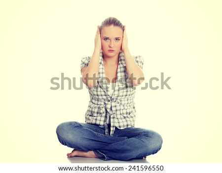 Young woman covering her ears. - stock photo