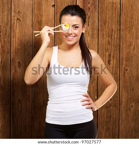 young woman covering her eye with a sushi piece against a wooden background