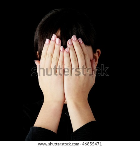 Young woman covering her eyes isolated on black background - stock photo