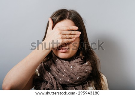 Young woman covering her eyes with her hand. On a gray background. - stock photo