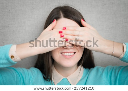 young woman covering her eyes with her hands in anticipation of something - stock photo