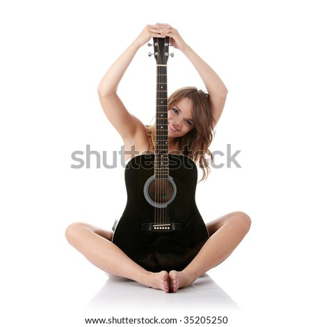 Young woman covering her self with black classic guitar isolated on white background - stock photo