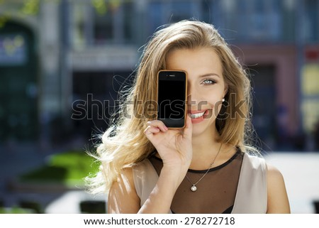 Young woman covers her face screen smartphone on a background of the city - stock photo