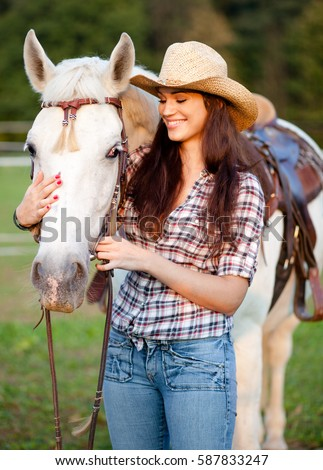 Young woman cowgirl caressing white horse