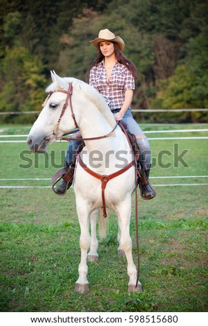 Young woman cowgirl riding white horse