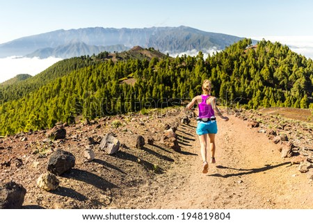 Young woman cross country running in mountains on sunny summer day. Beauty female runner jogging and exercising outdoors in nature, rocky trail footpath on La Palma, Canary Islands - stock photo
