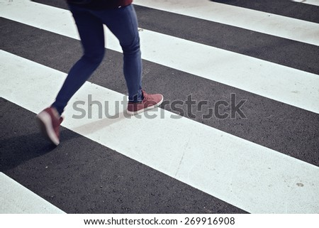 Young woman crossing a zebra crossing. - stock photo