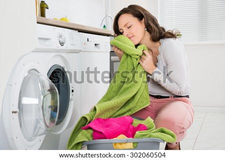 Young Woman Crouching With Cleaned Clothes Near The Electronic Washer - stock photo