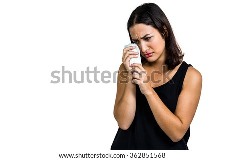 Young woman crying against white background - stock photo