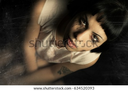 Young woman crying tears. Anxiety and sadness. A beautiful young girl crying tears. Concept of women's issues, youth issues. Black background and effect consumed scratched to highlight the confusion.