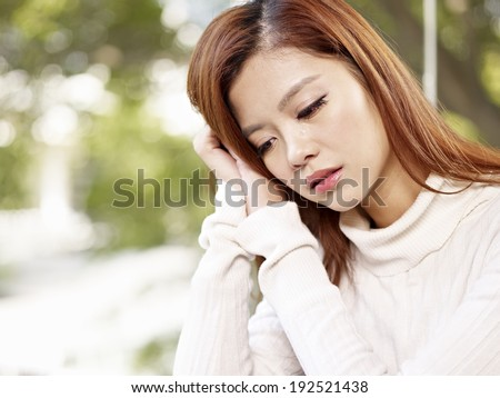 young woman crying with tears on face. - stock photo