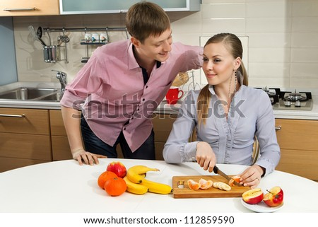 Young woman cutting fruits with her boyfriend on kitchen