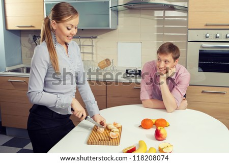 Young woman cutting fruits with her boyfriend on kitchen - stock photo