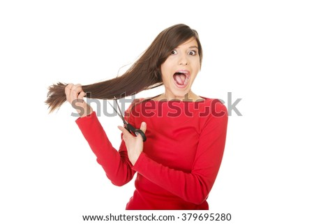 Young woman cutting her hair. - stock photo